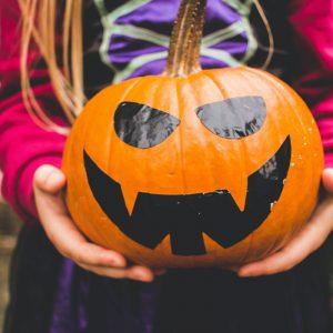 Child holding a Halloween pumpkin